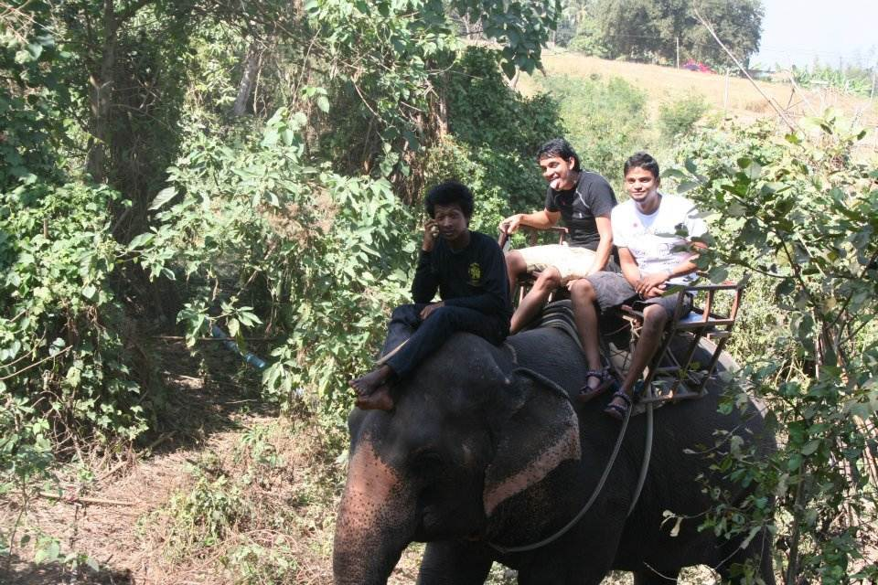 Arun and Bharath riding an elephant.