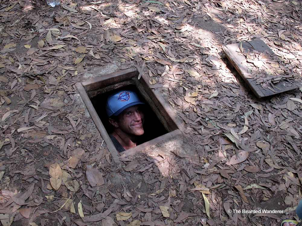 "An American tourist poses in a ""spider hole"" at the Cu Chi tunnels memorial. (Will Jackson)"