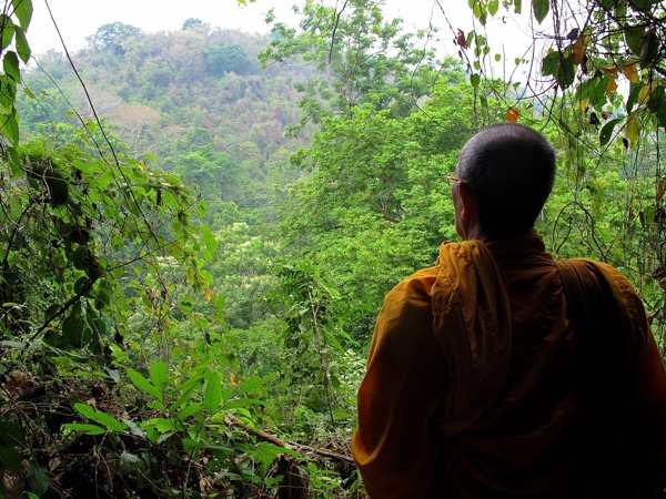 A monk looks out at the scenery above the Kuang Si Waterfalls. (Will Jackson)